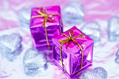 Shining colorful Christmas presents. Blue and purple Christmas gift and heart decorations stock image