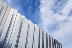 Shining corrugated metal fence and blue cloudy sky Stock Photos