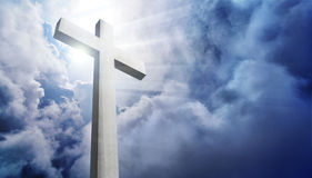 Shining cross in front of a dramatic cloudy sky royalty free stock images