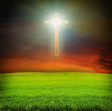 Shining cross over dark sky and field Stock Photos