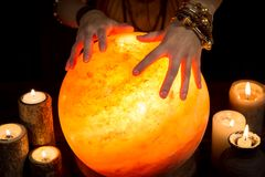 Shining crystal ball with candles and hands of a female fortune stock image