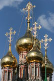 Shining domes of orthodox church. Shining golden domes of orthodox christian church with golden crosses against blue sky reflecting sun and clouds Royalty Free Stock Photos