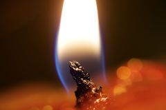 Shining flame. A flame is shining upon a red candle Royalty Free Stock Image
