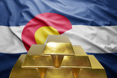 Colorado gold reserves. Shining golden bullions on the colorado flag background royalty free stock image