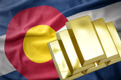 Shining golden bullions on the colorado state flag. Gold reserves. shining golden bullions on the colorado state flag background royalty free stock image