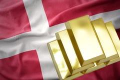 Shining golden bullions on the denmark flag. Gold reserves. shining golden bullions on the denmark flag background Stock Photography