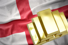 Shining golden bullions on the england flag. Gold reserves. shining golden bullions on the england flag background Stock Images