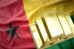 Shining golden bullions on the guinea bissau flag Stock Photo