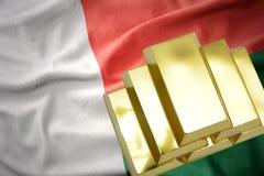 Shining golden bullions on the madagascar flag. Gold reserves. shining golden bullions on the madagascar flag background Royalty Free Stock Photos