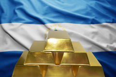 Nicaraguan gold reserves. Shining golden bullions on the nicaraguan flag background Royalty Free Stock Photography