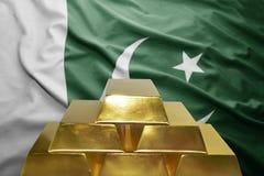 Pakistani gold reserves. Shining golden bullions on the pakistani flag background Royalty Free Stock Images