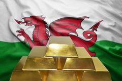 Welsh gold reserves. Shining golden bullions on the welsh flag background Royalty Free Stock Photo