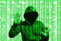 Shining green hacker behind computer code matrix. Computer code glowing binary matrix background with a hooded hacker holding up both hands shining through Royalty Free Stock Image