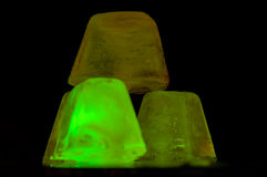 The shining ice. Three pieces of ice the lit lucho of green color on a black background Royalty Free Stock Image