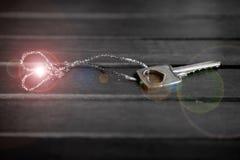 Shining key from heart Stock Photos