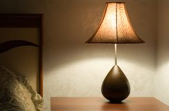 Shining lamp. On the table near bed Stock Image