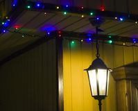 The shining lamp and garland on the house royalty free stock photo