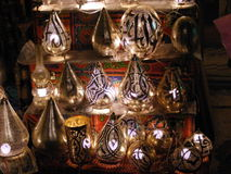 Shining lanterns in khan el khalili souq market with Arabic handwriting on it in egypt cairo. Vendor selling handmade copper oriental lamps ornaments in khan el Royalty Free Stock Image