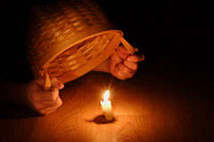 Shining Light (Biblical concept-Hiding your light under a bushel. Hands holding a basket over a burning candle Stock Image
