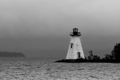 Shining lighthouse in B&W. A lighthouse stands out as a beacon in a cloudy setting. Black & white image Stock Images