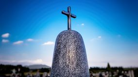 Shining metal cross on the top of the marble tombstone royalty free stock images