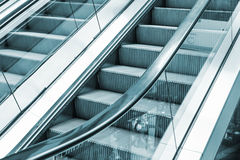 Shining metal escalator moving up, blue toned Stock Photo