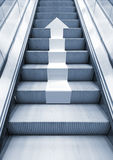 Shining metal escalator with white arrow moving up. Perspective effect, Blue toned 3d illustration combined with photo background Stock Image