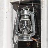 Shining metal kerosene lamp hangs on window Stock Photo