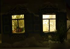 Shining New Year windows in the night. Christmas picture with shining windows with carved shutters Stock Image