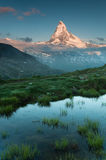 Shining peak of Matterhorn. Shining Matterhorn peak with the grass and water in foreground. Photo was taken from Stellisee Stock Photos