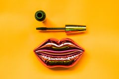 shining pink lips and mascara on bright yellow background, makeup and beauty concept stock photography
