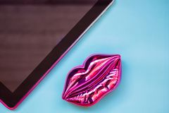 shining pink lips and touch pad on bright pink background, fashion and beauty concept stock photos