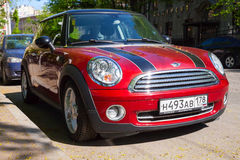 Shining red metallic mini cooper car. Saint-Petersburg, Russia - May 32, 2015: shining red metallic mini cooper car with black stripes stands on road side in the Royalty Free Stock Photo