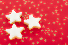 Shining star shaped cinnamon biscuits on red background Royalty Free Stock Photography