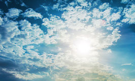 Shining sun with lens flare. Blue sky with clouds background Royalty Free Stock Image