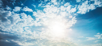 Shining sun with lens flare. Blue sky with clouds background Royalty Free Stock Photography