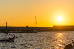 Shining sun over Alghero harbor at dusk. Italy Stock Photo