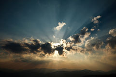 Shining sunrise over the mountains in a cloudy sky Stock Photo