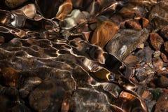 Coloured stones in a mountain creek. Shining texture of coloured stones in a clear mountain creek Stock Photos