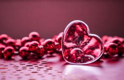 Shining transparent heart and a group of red beads. Perfect Valentine`s Day greeting card background. Horizontal image in pink. Tone stock photo