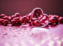 Shining transparent heart and a group of red beads. Perfect Valentine`s Day greeting card background. Horizontal image in pink. Tone stock image