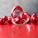 Shining transparent heart and a group of red beads. Perfect Valentine`s Day greeting card background. Image in red tone on grey. Background in a 1x1 format stock photography
