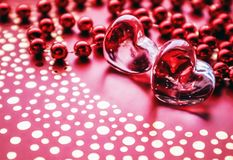 Shining transparent hearts and a group of red beads. Perfect Valentine`s Day greeting card background. Vertical image in red. Tone stock photos