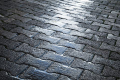 Shining wet cobblestone pavement, urban road Royalty Free Stock Images