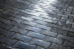 Shining wet cobblestone pavement, urban road Royalty Free Stock Images