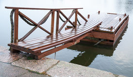 Shining wet wooden floating pier in still lake water Royalty Free Stock Photo
