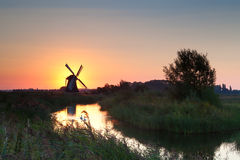 Shining windmill during sunrise over river Royalty Free Stock Photos
