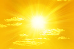 Shining Yellow Sun Sky. A yellow toned sun and sky with a few clouds Royalty Free Stock Photo