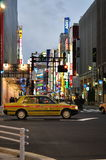 Shinjuku lights. Neon lights on storefronts of Shinjuku in Tokyo, Japan with a taxi driving pass royalty free stock image