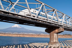 Shinkansen. Japanese high speed train going over river Fujikawa on Tōkaidō line. In the background is clearly visible Fuji-san, the highest mountain of Japan Royalty Free Stock Image